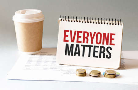 Hand with red pen. Cofee cup. Stick. Keyboard and white background. Everyone Matters sign in the notepad