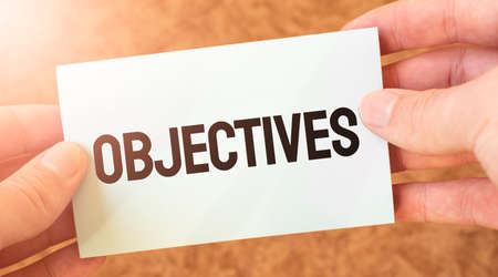 OBJECTIVES word inscription on white card paper sheet in hands of a businessman. recap concept. red and white paper