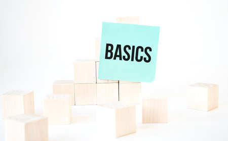 Text BASICS writing in green card cube ladder. White background. Business concept
