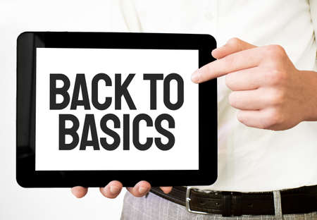 Text BACK TO BASICS on tablet display in businessman hands on the white bakcground. Business concept