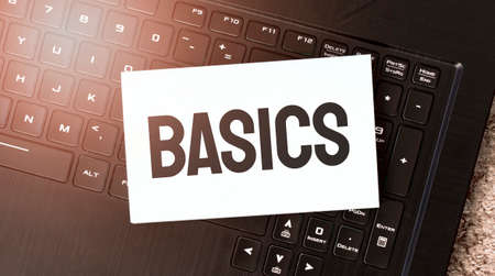 White paper sheet with text BASICS on the black laptop