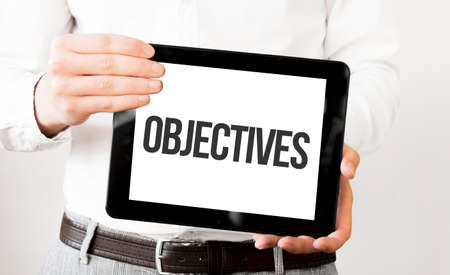 Text OBJECTIVES on tablet display in businessman hands on the white bakcground. Business concept