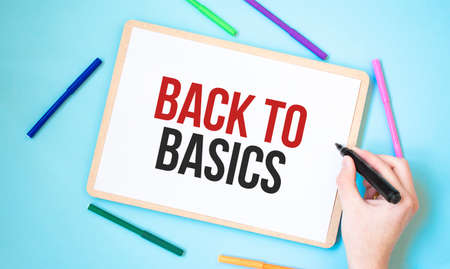 Text BACK TO BASICS on a notebook surrounded by colored felt-tip pens, business concept idea, Stock fotó