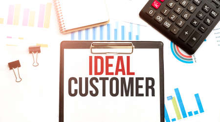Paper plate with text IDEAL CUSTOMER. Diagram, calculator, notepad and white background