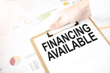 Text FINANCING AVAILABLE on white paper plate in businessman hands with financial diagram. Business concept Stock fotó