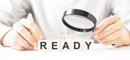 Businessman holding magnifier. Businessman watch on the wooden cubes with text READY. financial market. financing