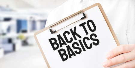 Text BACK TO BASICS on white paper plate in businessman hands in office. Business concept