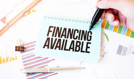 Businessman hand, paper plate, marker, diagram, chart and office tools. Text FINANCING AVAILABLE