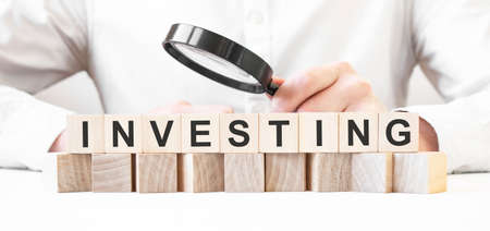 Businessman holding magnifier. Businessman watch on the wooden cubes with text INVESTING. financial market. financing Stock fotó