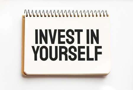 Notepad with text Invest in Yourself. White background. Business Stockfoto