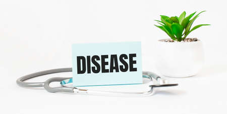 DISEASE word on notebook, stethoscope and green plant