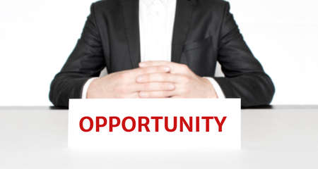Businessman sitting at the table and signboard with text Opportunity. Business concept