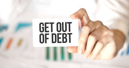 businesswoman holding a card with text get out of debt