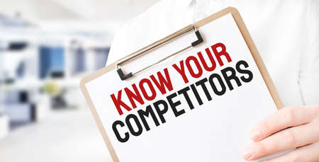 Text KNOW YOUR COMPETITORS on white paper plate in businessman hands in office. Business concept