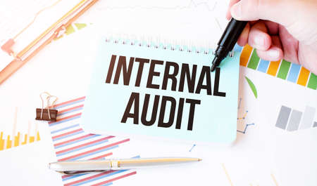 Businessman hand, paper plate, marker, diagram, chart and office tools. Text INTERNAL AUDIT