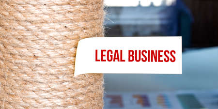 Torn brown paper on white surface with text LEGAL BUSINESS
