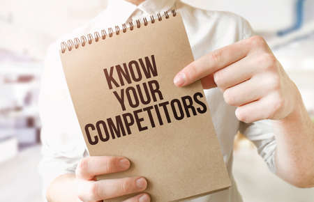 Text KNOW YOUR COMPETITORS on brown paper notepad in businessman hands in office. Business concept