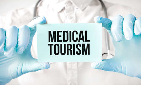 Doctor holding card in hands and pointing the word MEDICAL TOURISM