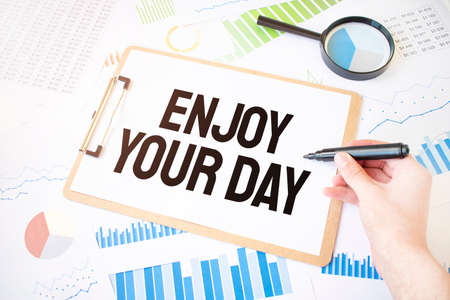 Text Enjoy Your Day on white paper sheet and marker on businessman hand on the diagram. Business concept
