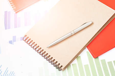 Close-up fountain pen over turnover graph paper it on wood desk in office.