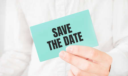 Businessman in white shirt holding a green card with text Save the Date