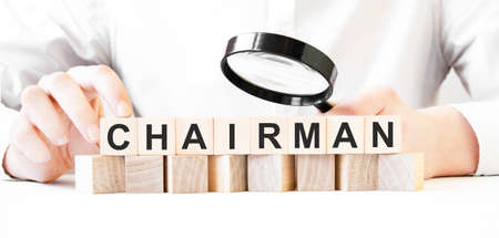 Businessman holding magnifier and wood block. Businessman watch on the wooden cubes with text CHAIRMAN. financial market. financing Stock fotó