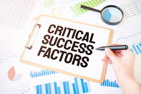 Text CRITICAL SUCCESS FACTORS on white paper sheet and marker on businessman hand on the diagram. Business concept
