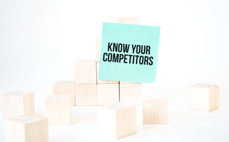Text KNOW YOUR COMPETITORS writing in green card cube ladder. White background. Business concept