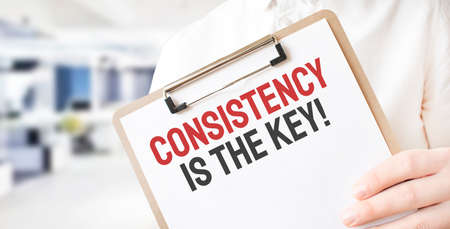 Text Consistency is the key on white paper plate in businessman hands in office. Business concept