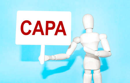 The wooden man holds a white sign with the text CAPA in his hands. The content of the lettering has implications for business concept and marketing.