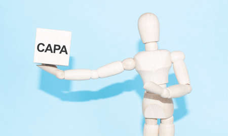 Business and design concept - wooden mannequin with surreal wood cube CAPA sign
