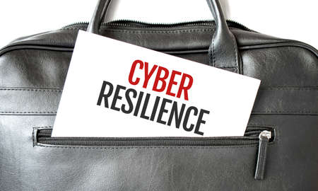 Text CYBER RESILIENCE writing on white paper sheet in the black business bag. Business concept