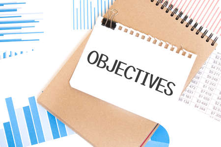 Text OBJECTIVES on white paper sheet and brown paper notepad on the table with diagram. Business concept
