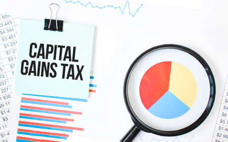 Green card on the white notepad and magnifier on the financial documentation. Text CAPITAL GAINS TAX. Business concept