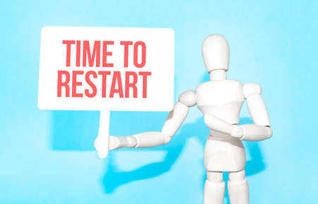 The wooden man holds a white sign with the text Time to Restart in his hands. The content of the lettering has implications for business concept and marketing.