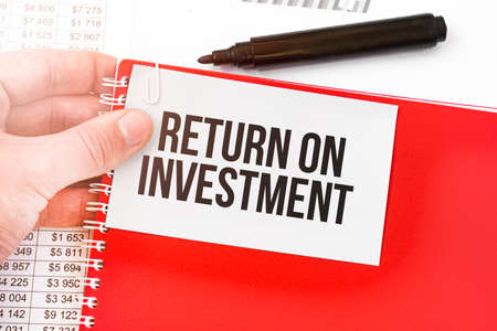 Business man holding a red notebook and white card with text return on investment. Financial concept