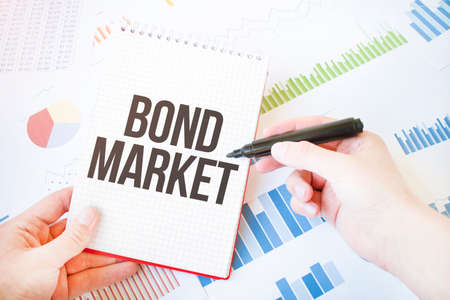 Notepad with text bond market. Diagram and white background