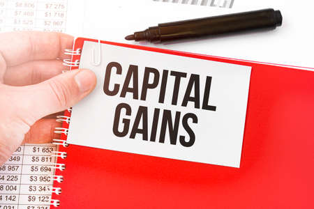 Business man holding a red notebook and white card with text CAPITAL GAINS. Financial concept