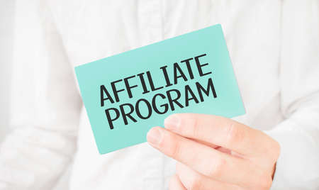 Businessman in white shirt holding a green card with text AFFILIATE PROGRAM