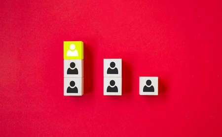 Wooden cube with person icon stand out from the crowd on red background. Dissenting opinion, divergent views and different concepts