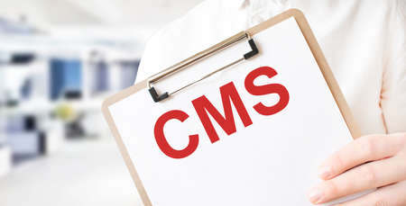 Text CMS on white paper plate in businessman hands in office. Business concept