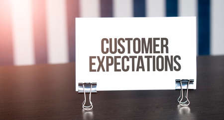 Customer Expectations sign on paper on dark desk in sunlight. Blue and white background