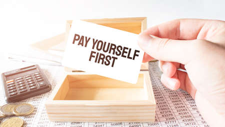 Businessman hold white card with text pay yourself first Calculator, wood box, money and financial documents Banco de Imagens