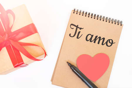 Valentine's day concept. Creaft gift box with red ribbon, pink wooden heart, black marker and craft color notepad with TI AMO sign Stock fotó