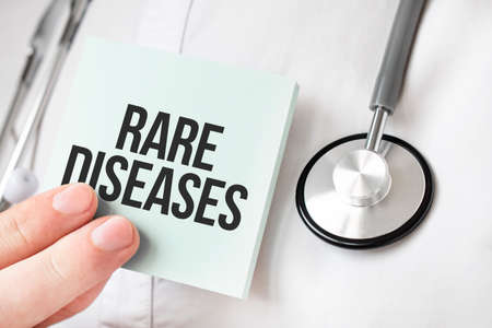Doctor holding card in hands and pointing the word RARE DISEASES Foto de archivo