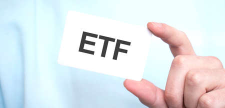 Man in blue sweatshirt holding a card with text etf, business concept