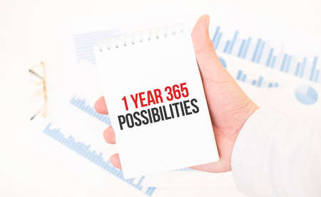 Businessman holding a white notepad with text 1 Year 365 Possibilities, business concept
