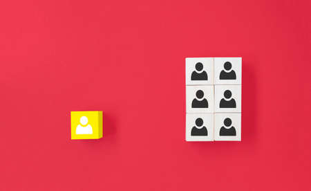 Yellow wooden cube with person icon stand out from the crowd on blue background. Dissenting opinion, divergent views and different concepts