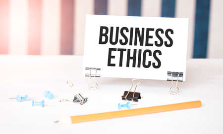 Business Ethics sign on paper on white desk with office tools. Blue and white background