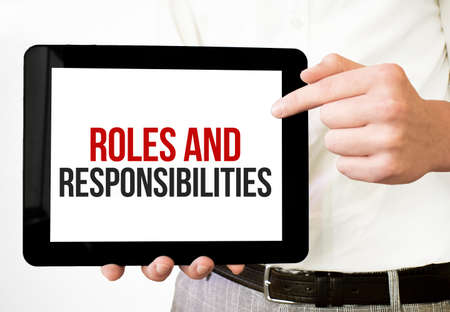 Text roles and responsibilities on tablet display in businessman hands on the white bakcground. Business concept